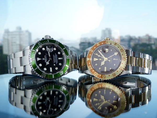 Two modern Rolex watches on a highly reflective table, with a background of a blurred cityscape skyline.