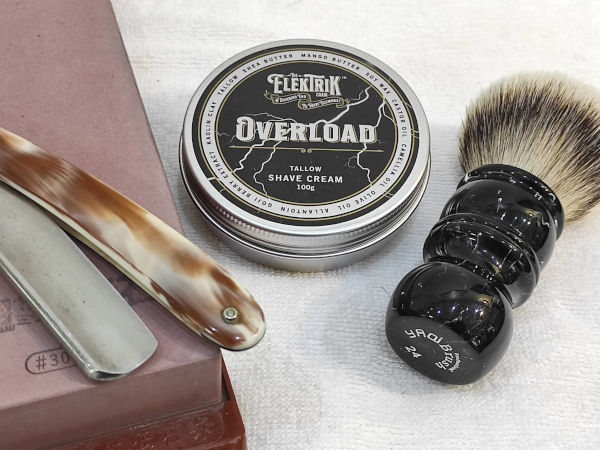 Close up of a straight razor resting on a honing stone, a badger hair shaving brush, and a tub of Overload shaving cream.