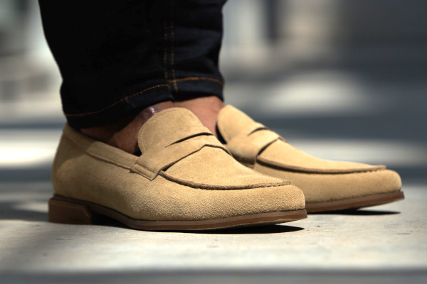A pair of penny loafers in tan suede.