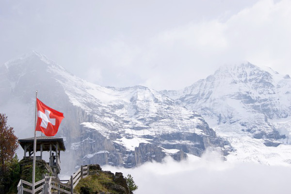Landscape view of the majestic Swiss Alps with snow capped mountains. Foreground of a mountain trek, safely guarded by wooden handrail, and the Swiss flag flying majestically.