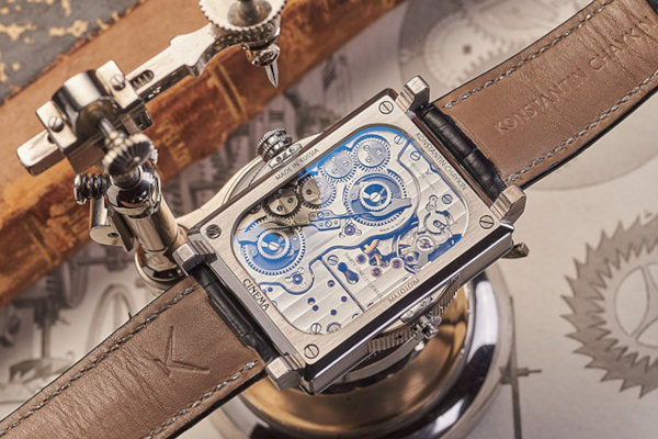 Close up view of a watch movement, encased in a watch, which is clamped down on a watch clamp, on a watchmaker's table.
