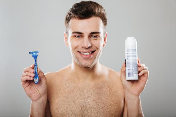 Man holding a cartridge razor and an aerosol shaving foam