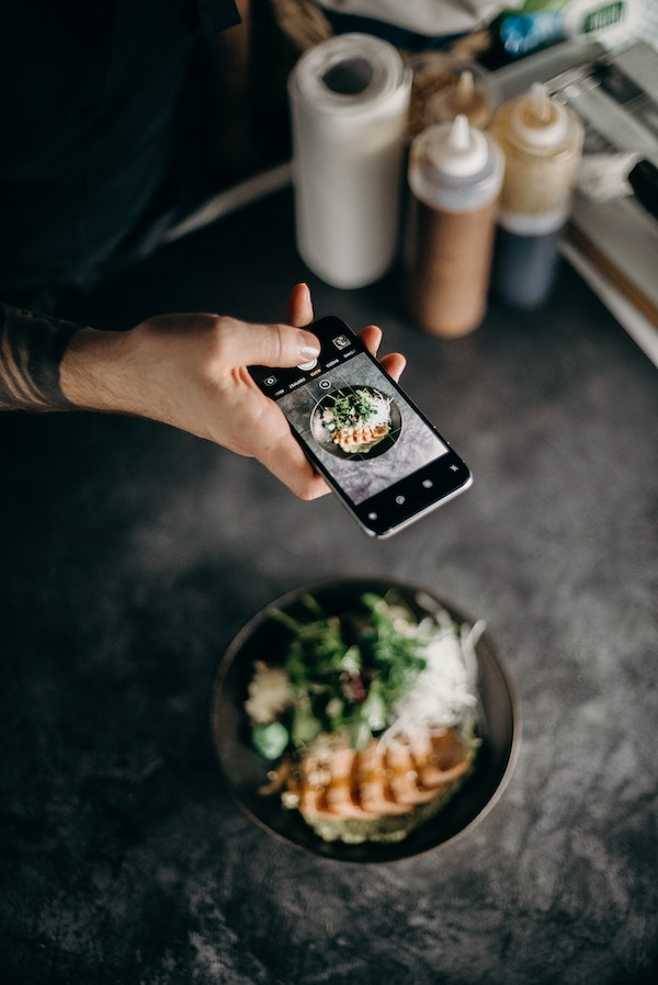 A person taking a photo of a bowl of food.