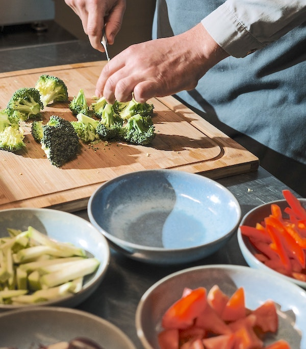 Small plates of various cut vegetables and someone cutting broccoli on a cutting board.