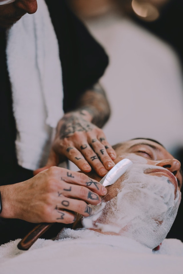A man getting a self pampering wet shave by a professional barber