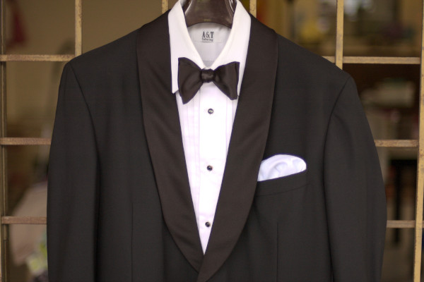 Close-up of a typical black tie ensemble - black dinner jacket with a shawl collar, dress shirt with pleated front, onyx shirt studs, and a black bow tie.