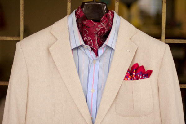 Close-up of the chest area, showcasing a red paisley day cravat, pale blue shirt with blue and red stripes, topped with an unbleached linen sport jacket.