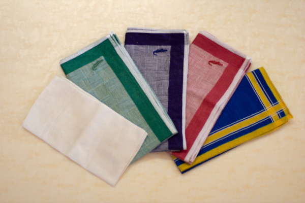 A spread of five handkerchieves on a table, showcasing the limited patterns and colours when compared to pocket squares.