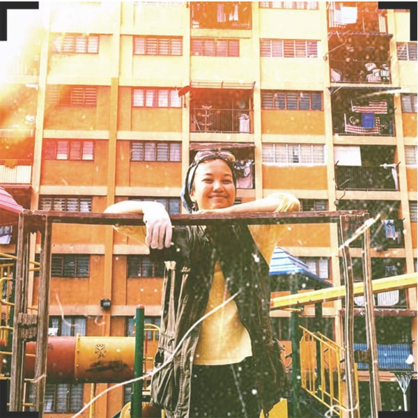 A picture of Natasya smiling at the camera with apartment buildings at the back.