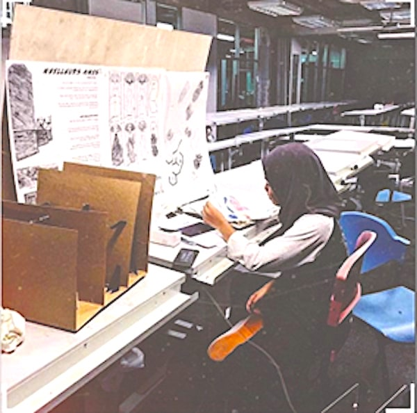 A photo of Natasya looking over her architectural works.