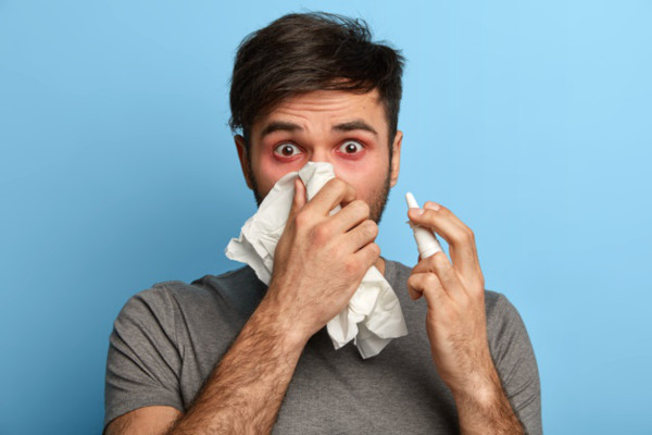 A man obviously suffering from some sort of flu, blowing his nose into a handkerchief, not a pocket square.