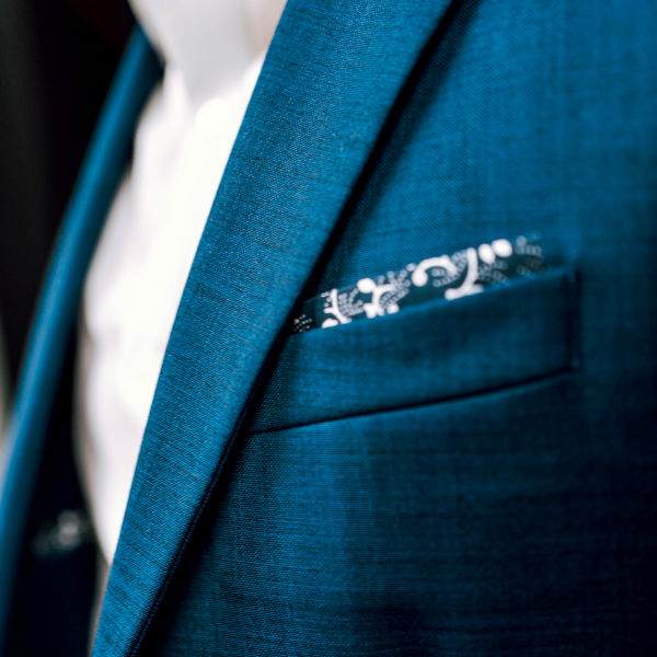 Close up of the chest area, showcasing a textured royal blue jacket and white shirt. A patterned pocket square in a square fold peeking out from the breast pocket.