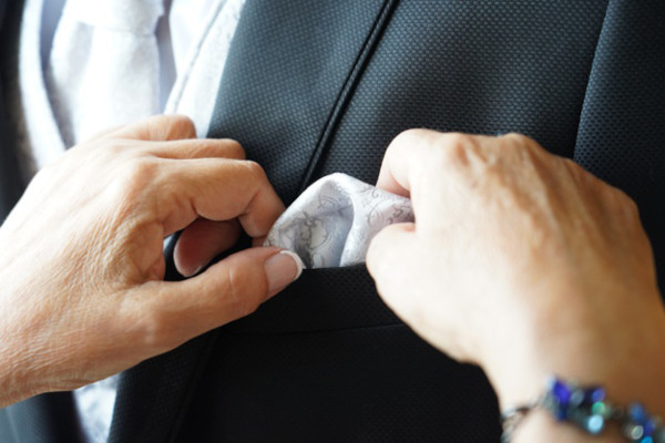 Close up of a woman (mother?) adjusting the pocket square in the breast pocket of a jacket (son?).