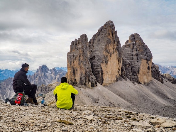 Two boys sitting looking out to a view of mountains and rocks after hiking.