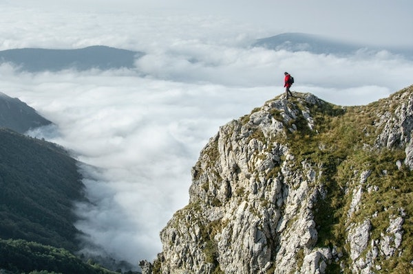 A man looking down from a cliff to a layer of clouds.
