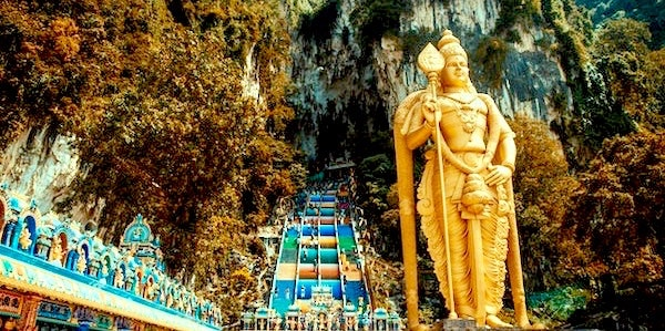A big golden statue of a Hindu idol and colourful stairs of a place called Batu Caves.