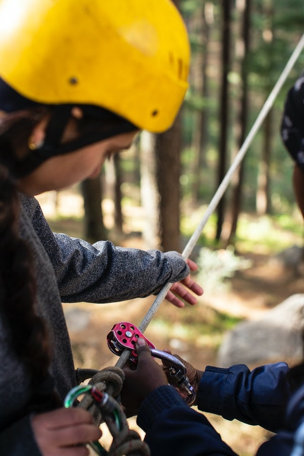 A woman teaching a girl how to work a harness and rope in an adventure park.