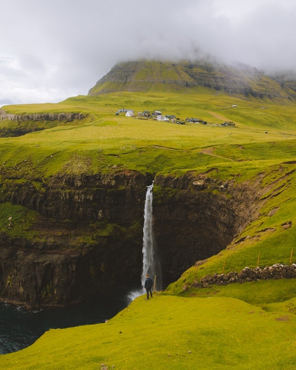 A man looking out to a green landscape of cliffs and mountains filled with waterfalls.