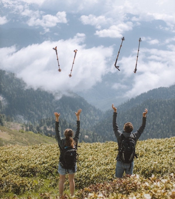 A man and a woman looking out to the forest on an adventure race of their own, throwing their hiking poles up in joy.