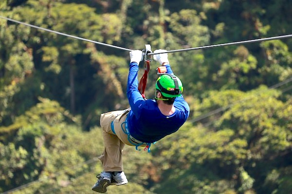 A man zip-lining into the forest in an adventure park.