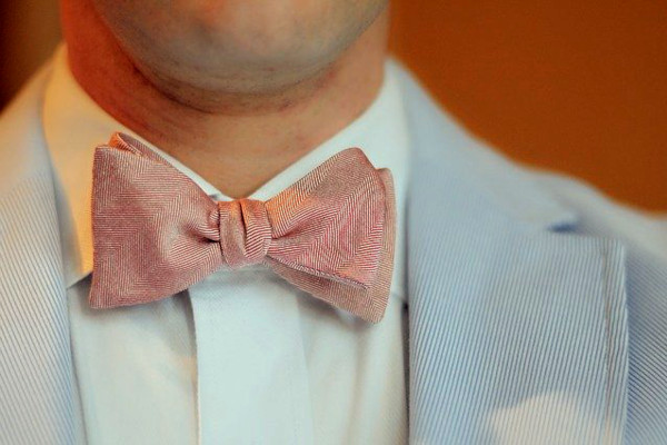 Close-up of a man's throat area, showcasing a pink bow tie matched with a solid white shirt and blue/white seersucker jacket.