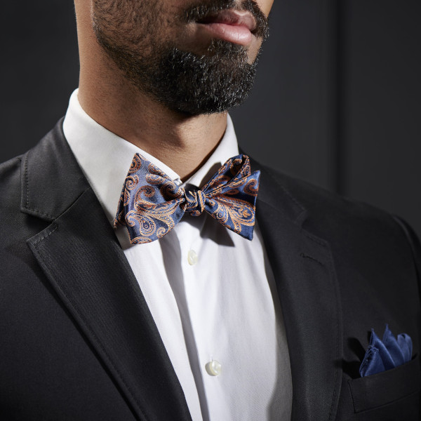 Close-up of a model wearing a navy/orange paisley bow tie with a solid white shirt and charcoal grey suit jacket.