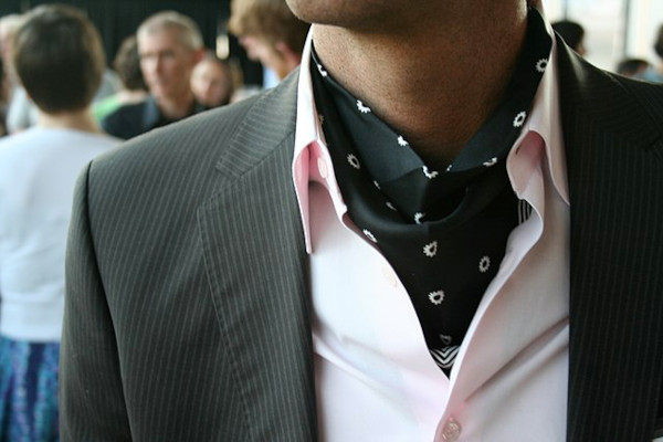 Close-up to the chest of a man wearing a pink, open necked shirt, and a small patterned, black day cravat underneath the collar, layered with a pin striped charcoal jacket.