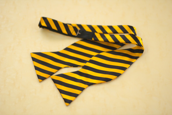 Close up of a self-tie bow tie, laid flat on the table, showcasing the adjustable neckband
