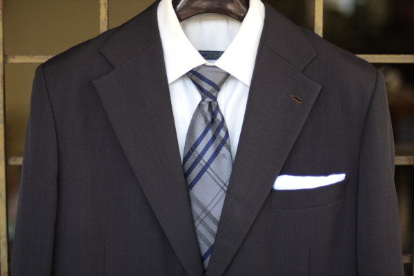 Close-up of the chest, showing a silver neckwear with navy and grey plaid on a charcoal suit jacket and solid white shirt.