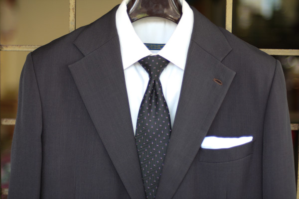 Close-up of the chest, showing a tie with small repeating pin dots on a charcoal suit jacket and solid white shirt.