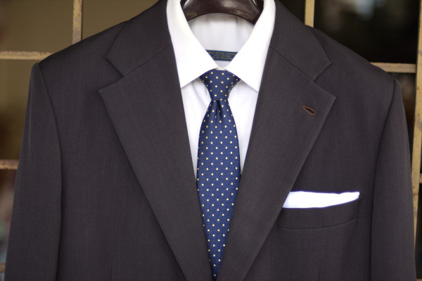 Close-up of the chest, showing a blue tie with yellow polka dots on a charcoal suit jacket and solid white shirt.