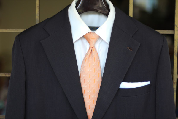 Close-up of the chest, showing a peach neckwear with repeating geometric patterns on a charcoal suit jacket and solid white shirt.