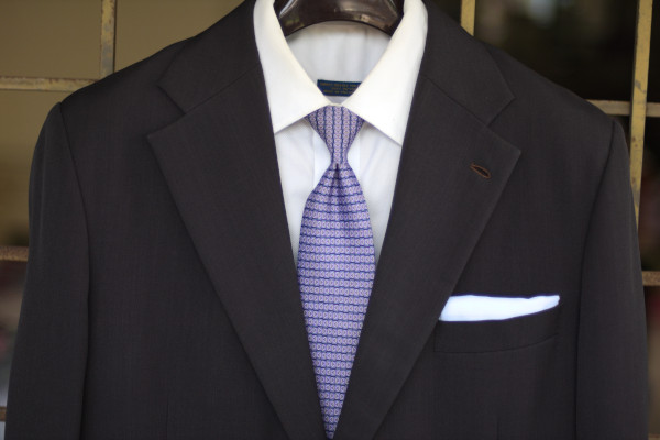 Close-up of the chest, showing a purple tie with small repeating geometric patterns on a charcoal suit jacket and solid white shirt.