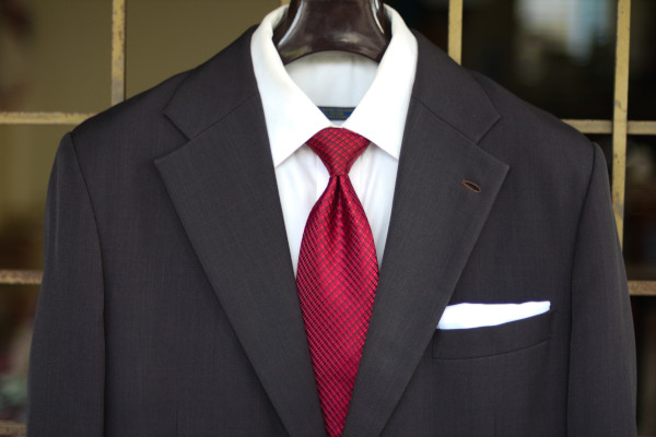 Close-up of the chest, showing a red tie with small repeating patterns on a charcoal suit jacket and solid white shirt.