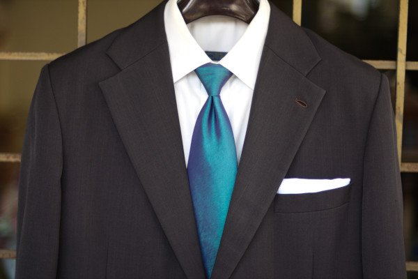 Close-up of the chest, showing a solid medium blue tie on a charcoal suit jacket and solid white shirt.