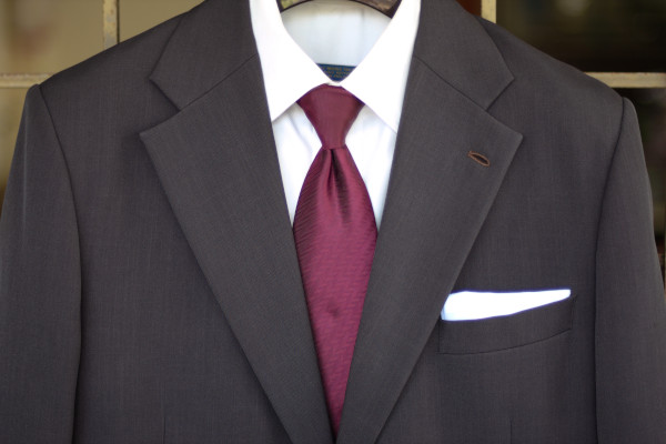 Close-up of the chest, showing a solid burgundy tie on a charcoal suit jacket and solid white shirt.
