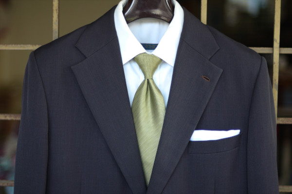 Close-up of the chest, showing a solid light green tie on a charcoal suit jacket and solid white shirt.