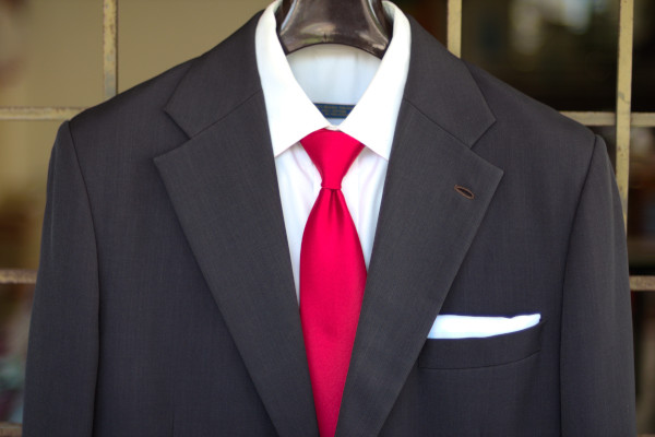 Close-up of the chest, showing a solid red tie on a charcoal suit jacket and solid white shirt.