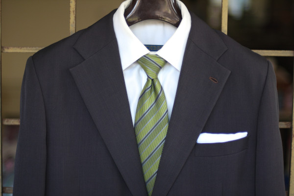 Close-up of the chest, showing a green tie with black regimental stripe on a charcoal suit jacket and solid white shirt.