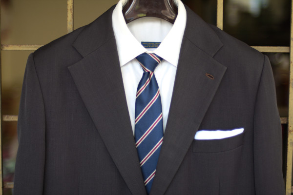 Close-up of the chest, showing a navy tie with white-red-white regimental stripes on a charcoal suit jacket and solid white shirt.