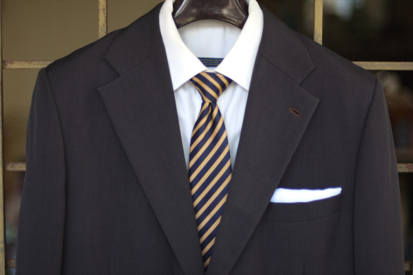 Close-up of the chest, showing a navy tie with yellow regimental stripes on a charcoal suit jacket and solid white shirt.