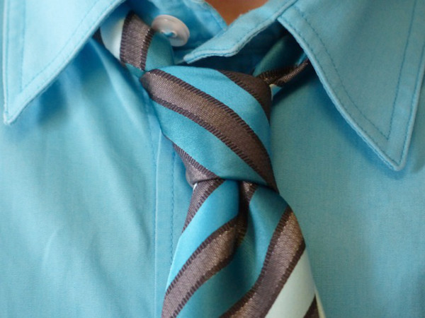 A loosely tied knot on an open collar pale blue shirt.