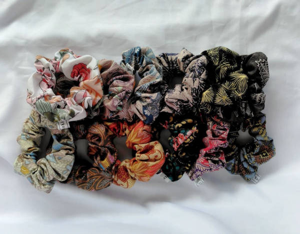 Two rows of batik scrunchies lying on top of a white cloth.