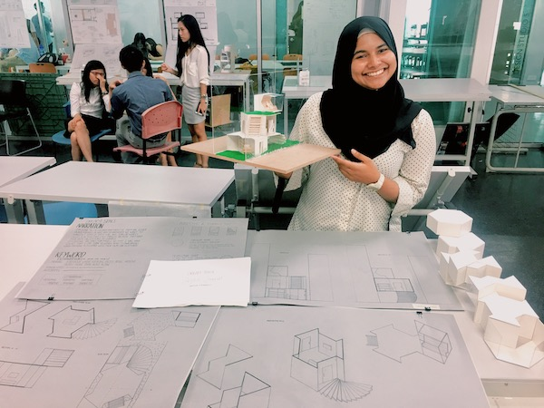 A picture of Salehah holding up her architecture physical model.