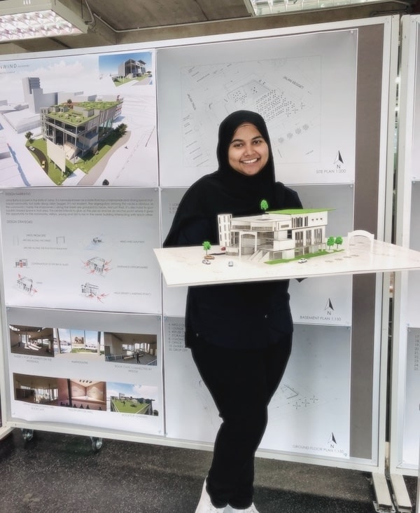 Picture of Sally holding up her physical architectural model during her final semester project.