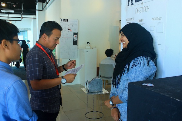 A picture of Salehah presenting her design to her lecturer, Mr Azim.