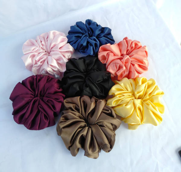 A total of seven fluffy, satin scrunchies in different colours laying on a white cloth.
