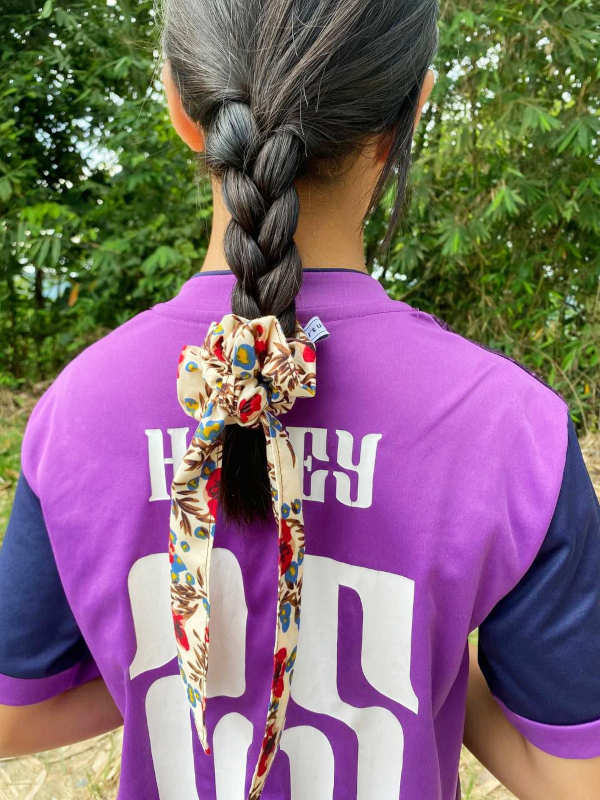 A photograph of a girl using the scrunchie with tails to secure her braided pigtail.