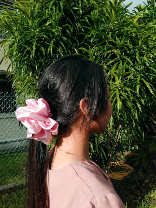 An image of a female model wearing a fluffy, pink satin scrunchie paired with a pink top.