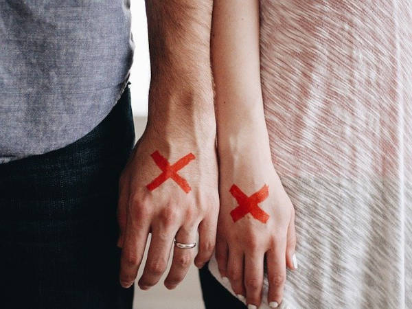 A couple with their hands marked with a X.